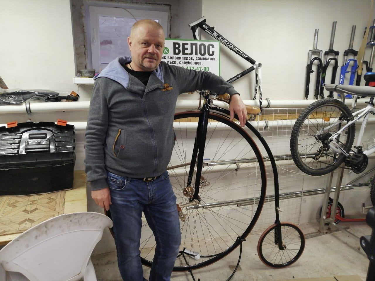 Мастер стоит рядом с велосипедом
